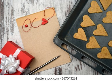 empty notepad with pen and red hearts on wooden surface, with gift box and cookies, Valentines day concept.