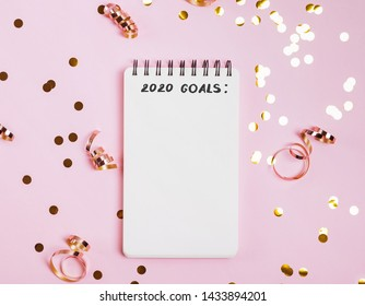 Empty notepad with place for text on the pink background with golden confetti, glitter and other festive decor.