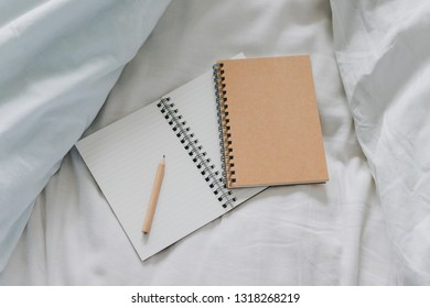 empty notepads with copyspace and pencil on messy bed sheets, concept of working from home or making plans in the morning
