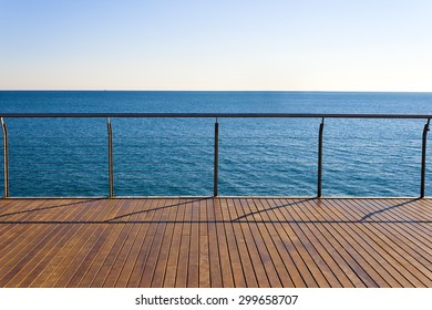 Empty ocean viewpoint platform with wooden floor desk. Clear sky and blue sea in a sunny day of summer. Horizontal composition.