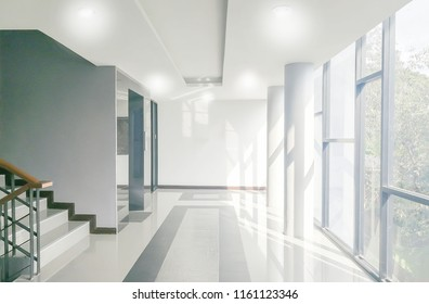 Empty office corridor with glass curtain wall, stair and light from sunlight. Modern building interior background, high key