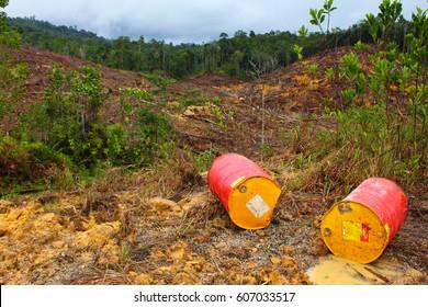 Empty oil barrels on deforested land