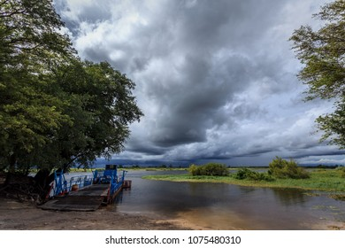Empty Okavango river ferry at shore with storm clouds