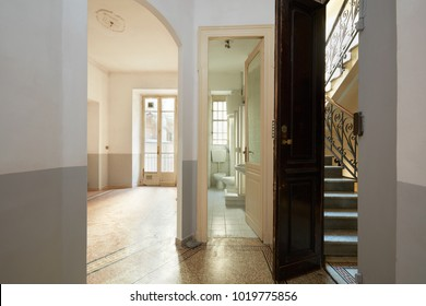 Empty, old apartment interior with bathroom, living room and staircase view