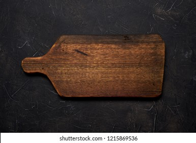 Empty old cutting board on a black background. Layout for the recipe.
