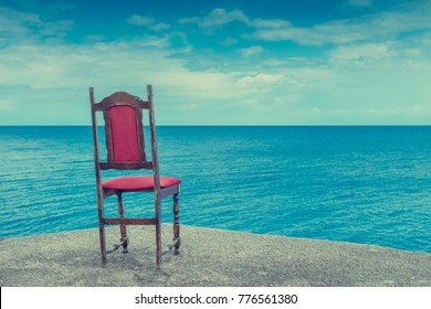 Empty old red chair standing on the sea shore