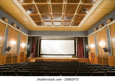 Empty old retro style cinema auditorium with line of chairs and stage with silver screen. Ready for adding your own picture.