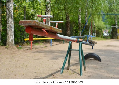 Empty old seesaw with chipped colors at children playground