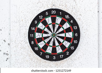 Empty old target dart board. Old used colorful board with lot of shots close up outdoors