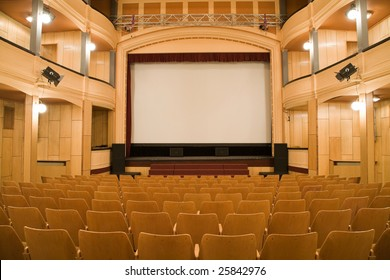 Empty old theater auditorium with arc line of chairs and stage with silver screen. Ready for adding your own picture.