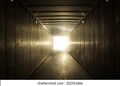 Empty old truck trailer with light at the end