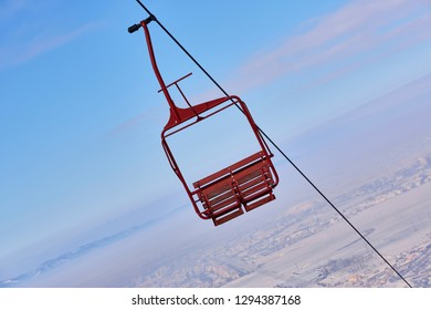 Empty old wooden chairlift against out of focus aerial urban area and blue sky. Brasov, Romania.