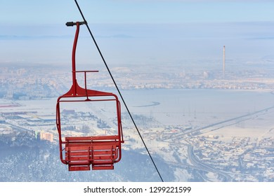 Empty old wooden chairlift against out of focus aerial urban area. Brasov, Romania.