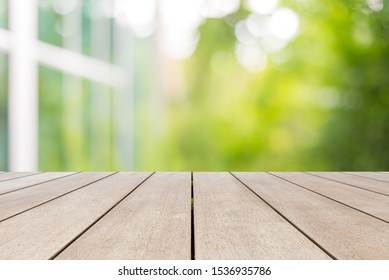 Empty old wooden table in front of abstract blurred bokeh background of nature. Can be used for display or montage for your products.