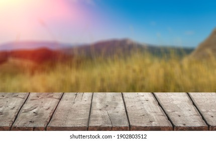 Empty old wooden table in front of blurred view on top of mountains and green field