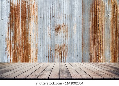 Empty old wooden table or wood floor for product placement or montage with old galvanize sheet background.