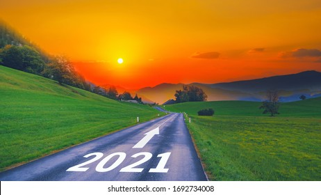Empty open asphalt road and New year 2021 concept. Driving on empty road goals against sun in mountains to upcoming 2021 and leaving behind old years. Concept for growth success, passing time future.