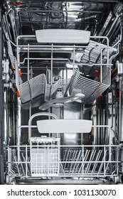 Empty open dishwasher ready for loading dishes for washing