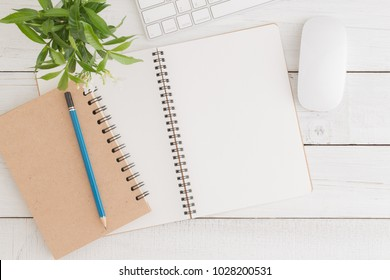 Empty open notebook on white wood table top view,Flat lay photo of office desk with mouse and keyboard