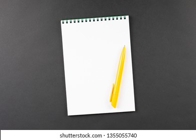 empty open notebook with yellow pen on black table top view. Desktop manager. Spiral notepad on an empty desk flat lay.