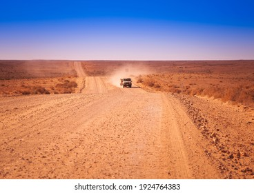 Empty open outback road in South Australia. Dirt road with lone truck stretching into the distance. Desert scene with a pure blue cloudless sky.