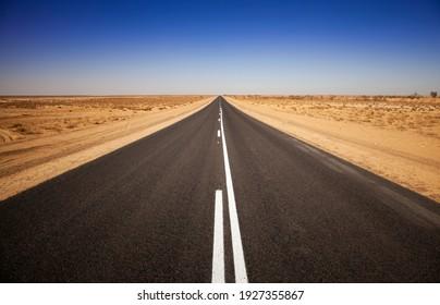 Route extérieure vide en Australie du Sud. Route asphaltée simple droite qui s'étend au loin. Scène désertique avec un ciel bleu pur et sans nuages. Voyage et aventure sans fin.