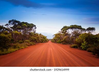 Une route extérieure vide en Australie occidentale. Chemin de terre à voie unique droit s'étendant au loin. Scène du désert, Voyage sans fin et aventure.