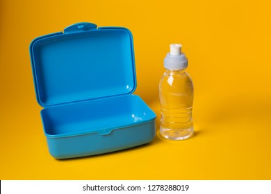 Empty open plastic lunch box and bottle of water, food container for school
