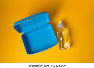 Empty open plastic lunch box and bottle of water, food container for school, top view