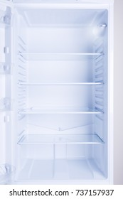 Empty opened modern refrigerator with clean glass shelves, nobody