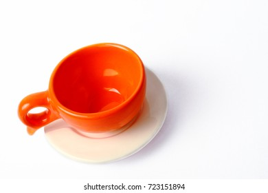 An empty orange cup with white plate isolated on white background.