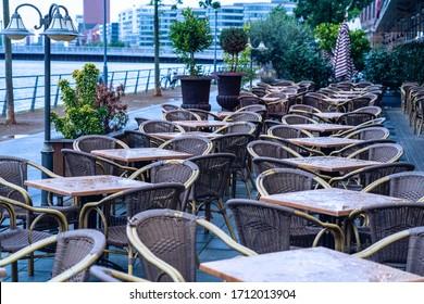 Leeres Café im Freien mit geschlossenen Regenschirmen. Straßencafé mit leeren Tischen und Stühlen. Möbelkonzept im Restaurant. Europäisches Café im Sommerterrasse. Sommerterrasse mit Tischen und freien Plätzen.
