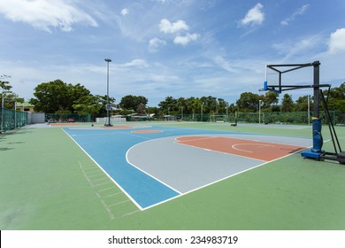 An empty, outdoor, colorful basketball court in Thailand with the sky and clouds in the background