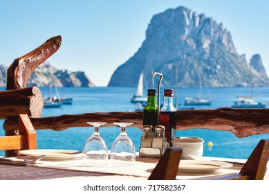 Empty outdoors restaurant, cafe with table chair setting at Cala d Hort beach with a fantastic view of mysterious island of Es Vedra and bay of Mediterranean sea. Ibiza Island, Balearic Islands. Spain