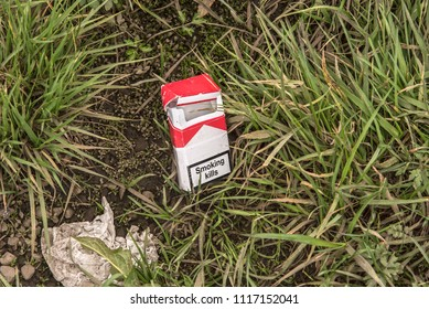 """An empty pack of cigarettes with the text, """"Smoking Kills"""" written on the front, littered in the grass. Taken in Iceland."""