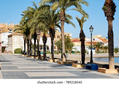 Empty palm lined seafront promenade of Los Alcazares, fishing village on Mar Menor in Murcia. Popular travel destinations for tourists, travellers and vacationers. Peaceful tranquil street Spain.