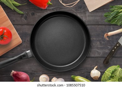Empty pan on a kitchen table surrounded by vegetarian cuisine ingredients.