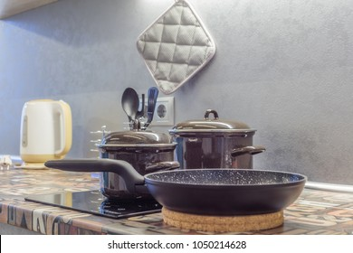 empty pan on stove with stands on table closeup