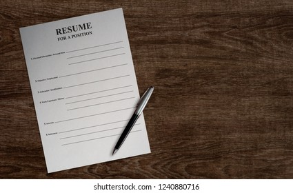 empty paper blank resume with ballpoint pen on wooden table background, job search concept, horisontal photo