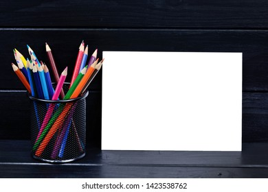 Empty paper with colorful pencils on black wood table