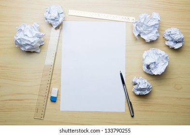 empty paper, crumpled paper and pen on wooden table