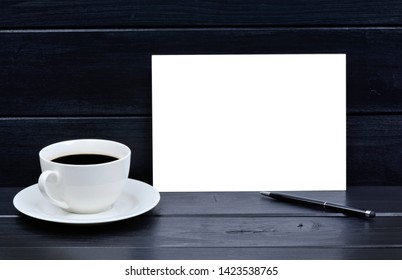 Empty paper with pen and coffee cup on black wooden table