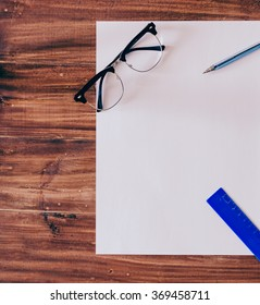 Empty paper, pen, glasses and ruler on the wood table