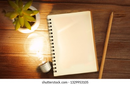Empty paper with pencil and idea light bulb on wood background