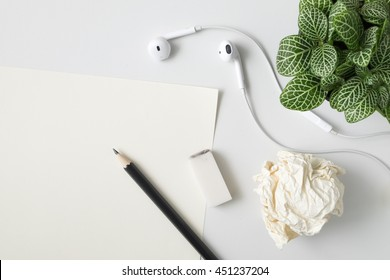 Empty paper, pencil, rubber, ear phone, crumpled ball and plant potted on white desk background