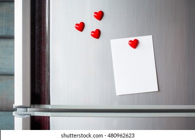 Empty paper sheet on refrigerator door. Note paper with magnetic heart. Valentine send text love message.