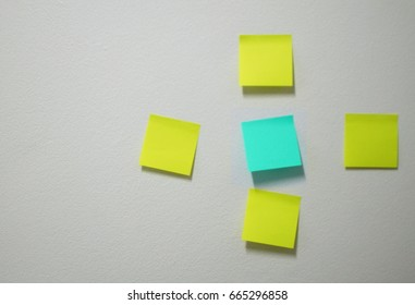 Empty paper sheet on white wall by yellow and blue color paper for add text  message or short note.