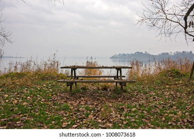 An empty park bench by the lake in winter.