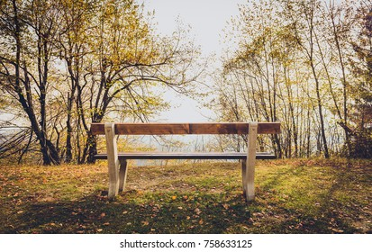 Empty park bench in mountain forest with idyllic golden view. Autumn golden colours in the woods with resting relaxation wooden bench and perfect view of nature and valley.