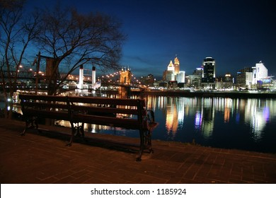 Empty park bench overlooking Ohio River and Cincinnati skyline.